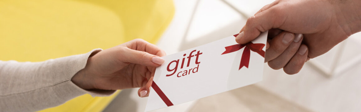 Cropped view of man giving gift card to woman, panoramic shot