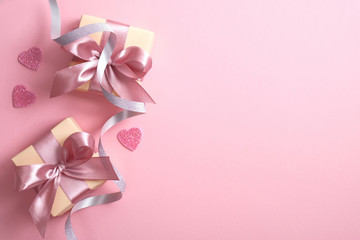 Valentine's day composition with gift box, hearts and ribbon on pink background. Flat lay, top view, copy space. Greeting card mockup for Valentine's Day, Happy Women's day, Mother's Day.