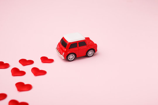 Red retro toy red car with red bow for Valentine's day on pink background with heart confetti