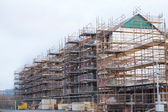 Building affordable homes with scaffolding safety by local construction council to help government social housing problem and shortage England UK