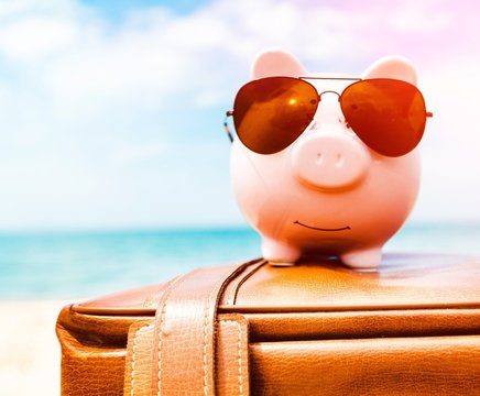 Pink piggy bank in sunglasses on leather travel case over sea beach