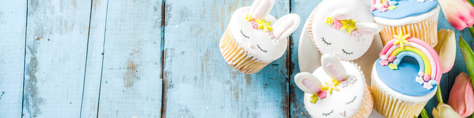 Easter holiday greeting card background. Cute homemade cupcakes with traditional Easter bunny, egg and springtime flowers decor. Happy easter concept. Copy space for your text