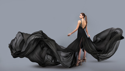 beautiful young girl in flying black dress. Flowing fabric. Light black fabric flying in the wind