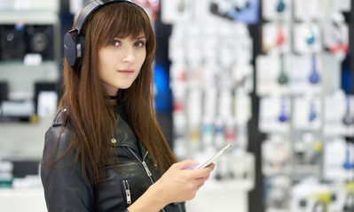 Photo sur Plexiglas Magasin de musique Portrait of a beautiful dark-haired girl with headphones in an electronics store. Shopping, gadgets, device.