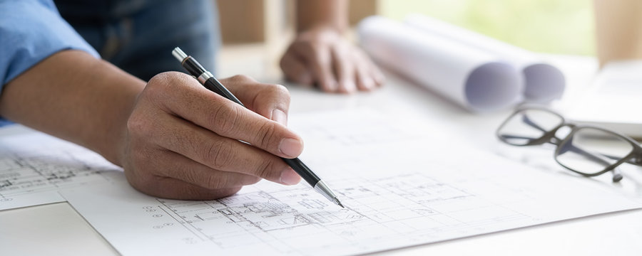 Architect or Engineer working in office with engineering tools, blueprint and building model. Construction concept.