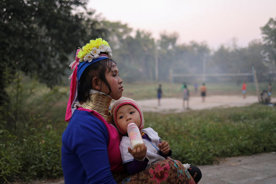 An ethnic Kayan hill tribe refugee woman, also known as long neck woman, sits with her baby inside their tourist attraction village near Chiang Mai