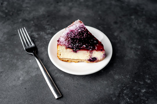 Currant cheesecake on a white plate on a stone background, ready to eat