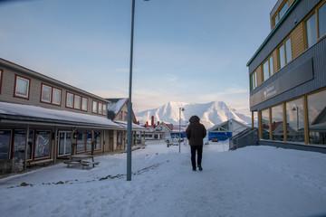 Longyearbyen, Svalbard in Norway - March 2019: Man walking in the street in Longyearbyen.
