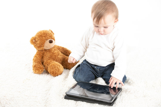 Studio photo with a white background of a baby looking at the screen of a tablet