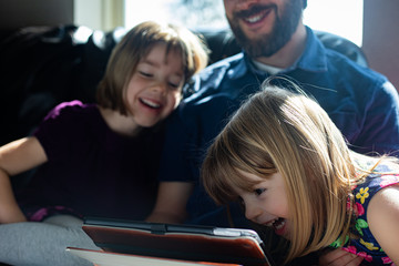 Father sits with daughter on technology watching tablet