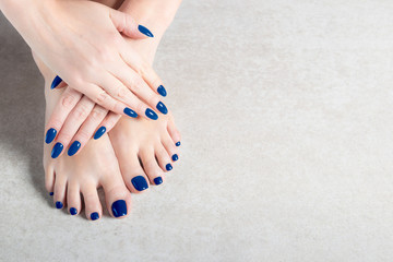 Young lady is showing her blue manicure and pedicure nails, grey background, copy space