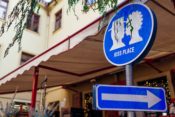 Kiss place sign in Lviv outdoor cafe. Kissing couple picture and arrow. Traveling and tourism, places of interest