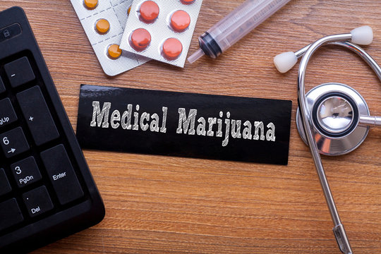 Medical Marijuana words written on label tag with medicine,syringe,keyboard and stethoscope with wood background,Medical Concept