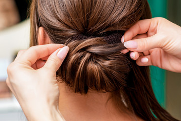 Spoed Fotobehang Kapsalon Rear view of hairdresser hands making hairstyle for woman in beauty salon, close up.