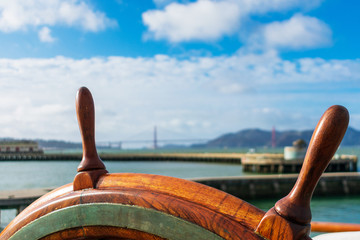 Close up. Ship steering wheel with blurred pier, Golden Gate Bridge and seascape background on the cloudy horizon