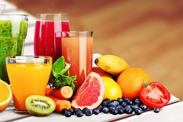 Poster Juice Composition of fruits and glasses of juice on blurred natural background