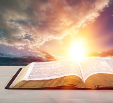 Holy Bible book on a sunset background