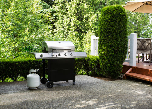 Outdoor cooker on House concrete patio with home deck on side