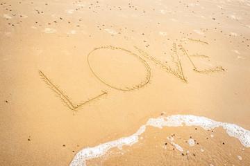Napis Love na piasku na plaży.