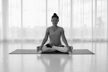 woman sitting on lotus position on floor legs crossed with eyes closed for meditating in room. Yoga at home.