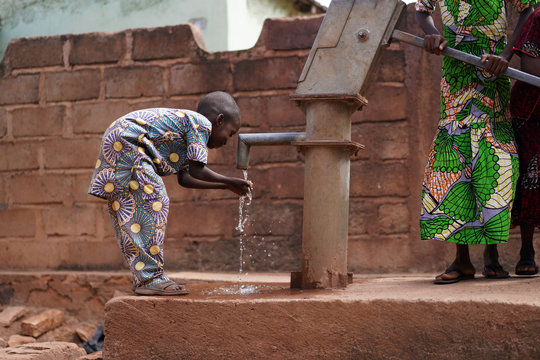Little African Boy Drinking Fresh Water From The Village Borehole