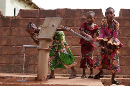 Three Eager Little African Girls Trying Out Their Village Water Pumping Station