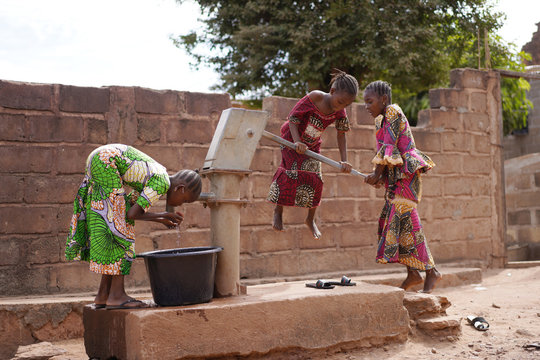African Girls Having Trouble In Pumping Water Out Of An Almost Dry Public Well