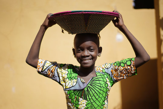 Cute African Girl Carrying a Couloured Handmade Straw Basket On Her Head