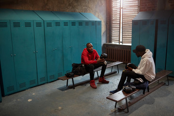 Two African boxers sitting on bench taking their boxing gloves from bags and preparing for the training in locker room