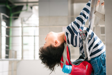 Little Asian hyperactive difficult boy hold handrail and lean body and head backwards, carry red backpack and insulated water bottle due to Autism, Behavioral and Attention Deficit Disorder.
