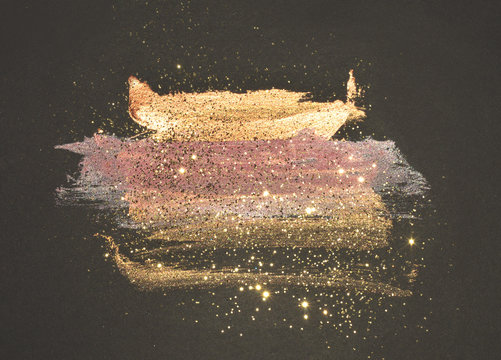 Glitter on abstract golden and pink watercolor stains on black background for your design