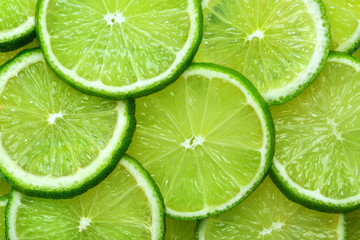 Close-up juicy Lime slices abstract background in pastel green color. Bright summer texture. Wall mural