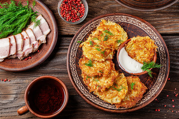 Ukrainian food. A grated potato dish of Deruny or Draniki grated on a clay plate. Serving dishes in a restaurant. Copy space, background image
