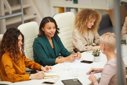 Group of businesswomen having meeting in modern office horizontal high angle shot