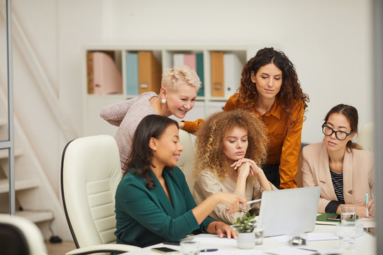 Group of five positive stylish women using laptop to work on project during business meeting horizontal shot