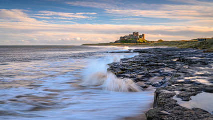 Crashing Waves at Bamburgh Beach, and dunes which are dominated by the imposing medieval castle and located within Northumberland Coast Area of Outstanding Natural Beauty
