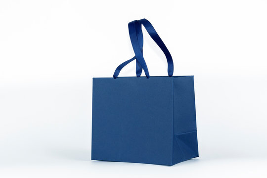 Gift paper bag, shopping bag in classic blue color isolated on white background. Mockup of blank craft package. Concept for presents holidays, father's day