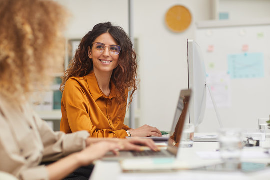 Two beautiful female colleagues interacting while working in office