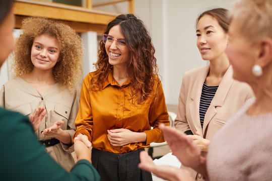 Group of friendly women clapping hands and congratulating their colleague on getting career promotion