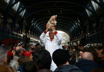 A butcher holds up a piglet for sale during a Christmas Eve auction in Smithfield market in London