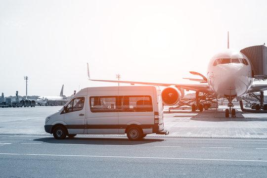 White VIP service van running on airport taxiway with big passenger airplane on background. Business class service at airport. Security intelligence agency hurrying at airfield