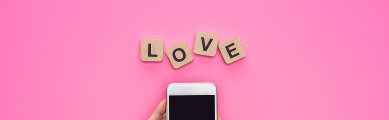 partial view of woman holding smartphone near cubes with love lettering on pink background, panoramic shot