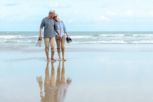 Lifestyle asian senior couple happy walking hug and relax on the beach.  Tourism elderly family travel leisure and activity after retirement in vacations and summer.