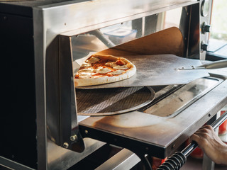 Cooking in modern pizza oven in cafe kitchen