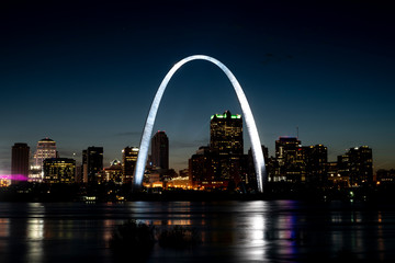 St Louis Gateway Arch brightly lit and shining at night, city skyline in background, reflecting in Mississippi River