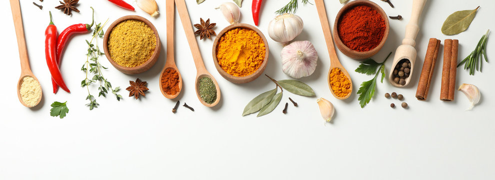 Spoons and bowls with different spices and ingredients on white background, space for text