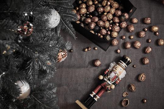 Nutcracker among golden walnuts and x-mas tree flat lay