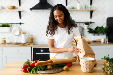 Smiled beautiful mulatto girl is putting packages with  food on the table on the modern kitchen Papier Peint