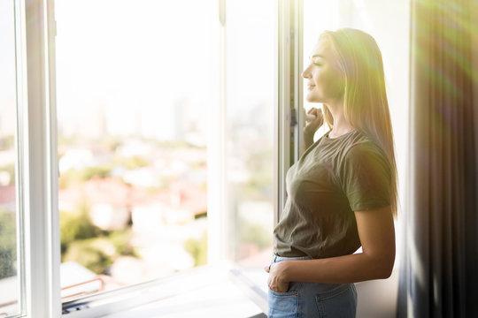 Happy woman open plastic windows for fresh air indoor