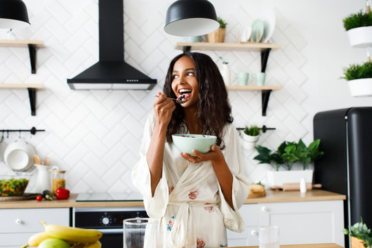 Smiled attractive mulatto girl is eating cutted fruits on white modern kitchen dressed in nightwear with messy loose hair